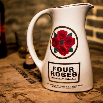 This pitcher was used as a promotional barware item. The circle and the enclosed cluster of roses became an iconic symbol for the brand.