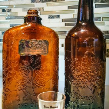 The one-quart bottle was produced after Prohibition, but lacks the no fill statement on the back, and the taller bottle is pre-Prohibition since it references the Paul Jones Company, Louisville, KY on the front. The shot glass is from the 1950s.